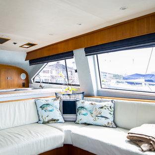 Modelo de salón abierto, marinero, pequeño, con paredes azules, suelo de madera en tonos medios, pared multimedia y suelo naranja