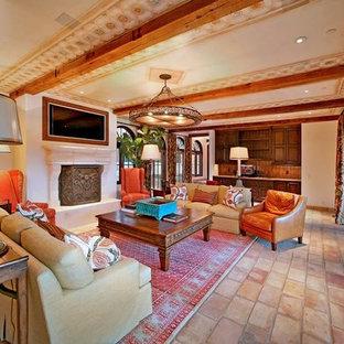 オレンジカウンティの中サイズの地中海スタイルのおしゃれな独立型リビング (白い壁、テラコッタタイルの床、標準型暖炉、漆喰の暖炉まわり、埋込式メディアウォール、ベージュの床) の写真
