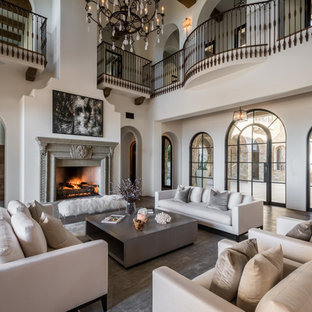 ロサンゼルスの地中海スタイルのおしゃれなリビング (フォーマル、ベージュの壁、濃色無垢フローリング、標準型暖炉、テレビなし、茶色い床) の写真