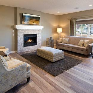 Imagen de salón abierto, moderno, grande, con paredes marrones, televisor colgado en la pared, suelo de madera en tonos medios, chimenea tradicional y marco de chimenea de piedra