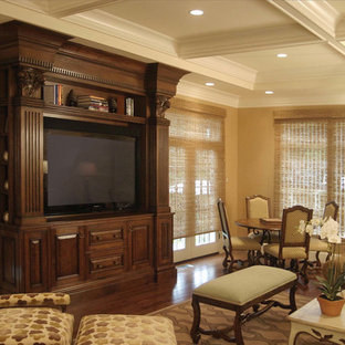 Example of a large classic enclosed dark wood floor and brown floor living room design in Boston with beige walls and a media wall