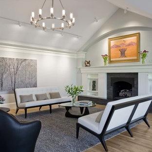 Foto di un soggiorno design di medie dimensioni e aperto con pareti bianche, camino classico, sala formale, parquet chiaro, cornice del camino piastrellata, nessuna TV e pavimento marrone