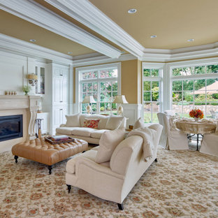 Elegant open concept carpeted, beige floor, tray ceiling and wainscoting living room photo in Boston with yellow walls and a standard fireplace