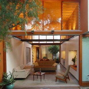 シドニーの中サイズのトロピカルスタイルのおしゃれなリビング (白い壁、コンクリートの床、内蔵型テレビ) の写真