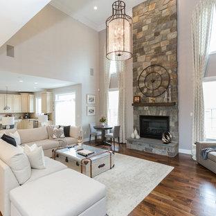 Bild på ett mycket stort vintage vardagsrum, med grå väggar, mellanmörkt trägolv, en standard öppen spis, en spiselkrans i sten och brunt golv