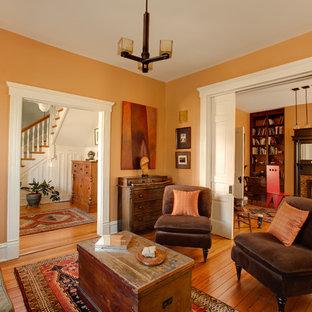 Immagine di un piccolo soggiorno boho chic chiuso con libreria, pareti arancioni, pavimento in legno massello medio, camino classico, cornice del camino piastrellata e nessuna TV