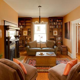 リッチモンドの小さいエクレクティックスタイルのおしゃれな独立型リビング (ライブラリー、オレンジの壁、無垢フローリング、標準型暖炉、タイルの暖炉まわり、テレビなし) の写真