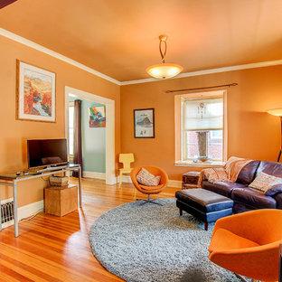 Diseño de salón tradicional, de tamaño medio, con parades naranjas, suelo de madera en tonos medios y televisor independiente