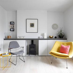 Foto di un soggiorno nordico di medie dimensioni e chiuso con libreria, pareti bianche, nessuna TV, pavimento in legno massello medio e pavimento beige