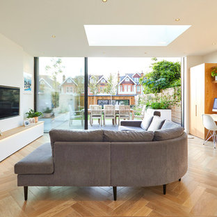 Design ideas for a medium sized contemporary open plan living room in London with white walls, medium hardwood flooring, a wall mounted tv and brown floors.