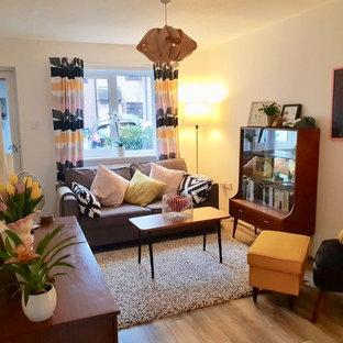 Immagine di un soggiorno scandinavo di medie dimensioni e chiuso con sala formale, pareti beige, pavimento in bambù, nessun camino, TV autoportante e pavimento marrone