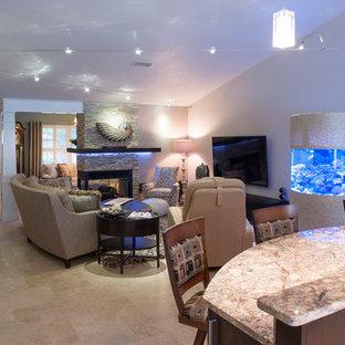 Immagine di un soggiorno design di medie dimensioni e aperto con pareti verdi, pavimento in travertino, camino ad angolo, cornice del camino in pietra e TV a parete