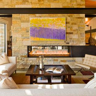 デンバーの大きいコンテンポラリースタイルのおしゃれなLDK (ベージュの壁、無垢フローリング、両方向型暖炉、石材の暖炉まわり、テレビなし) の写真