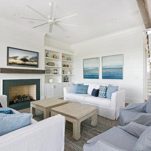 チャールストンの中サイズのビーチスタイルのおしゃれなLDK (白い壁、塗装フローリング、標準型暖炉、石材の暖炉まわり、壁掛け型テレビ、茶色い床) の写真