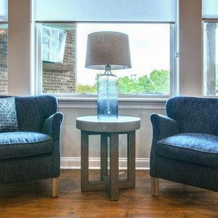 Mittelgroßes, Offenes Klassisches Wohnzimmer mit braunem Holzboden, Kamin, Kaminumrandung aus gestapelten Steinen, Wand-TV, braunem Boden und freigelegten Dachbalken in Nashville