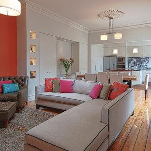 Idée de décoration pour un grand salon design ouvert avec un mur orange et un sol en bois brun.