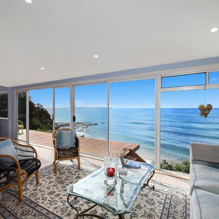 This is an example of a beach style formal open concept living room in Sydney with blue walls and light hardwood floors.