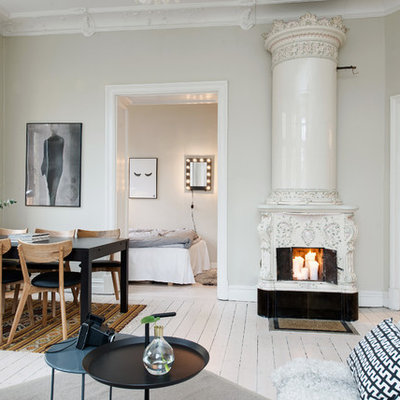 Large danish formal painted wood floor living room photo in Gothenburg with beige walls and a wood stove