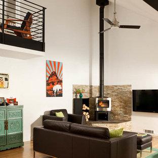 Diseño de salón abierto, contemporáneo, pequeño, con paredes blancas, suelo de madera clara, chimenea de esquina, marco de chimenea de piedra, televisor colgado en la pared y suelo marrón