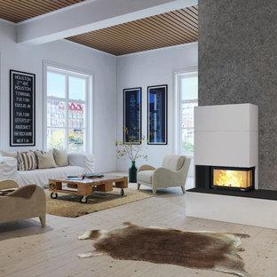 Imagen de salón abierto, nórdico, grande, con paredes grises, suelo de madera clara, estufa de leña y marco de chimenea de hormigón
