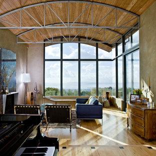 Diseño de salón con rincón musical abierto, moderno, grande, sin televisor, con paredes grises, suelo de madera clara, chimenea tradicional, marco de chimenea de piedra y suelo beige