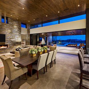 Cette image montre un grand salon sud-ouest américain ouvert avec une salle de réception, un mur beige, béton au sol, une cheminée ribbon, un manteau de cheminée en pierre, un téléviseur fixé au mur et un sol gris.