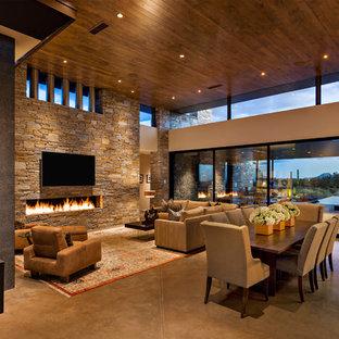 フェニックスの広いサンタフェスタイルのおしゃれなLDK (フォーマル、ベージュの壁、コンクリートの床、横長型暖炉、石材の暖炉まわり、壁掛け型テレビ、グレーの床) の写真
