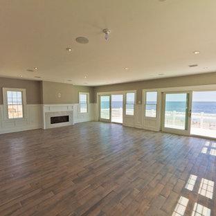 ニューヨークの大きいビーチスタイルのおしゃれなLDK (淡色無垢フローリング、標準型暖炉、石材の暖炉まわり、白い床) の写真