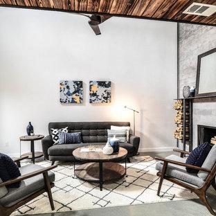 オースティンのインダストリアルスタイルのおしゃれなリビング (グレーの壁、コンクリートの床、標準型暖炉、コンクリートの暖炉まわり、グレーの床) の写真