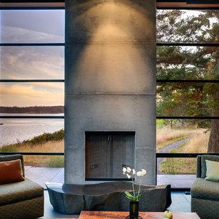 Immagine di un soggiorno moderno di medie dimensioni e aperto con cornice del camino in cemento, pareti grigie, pavimento in ardesia e camino classico