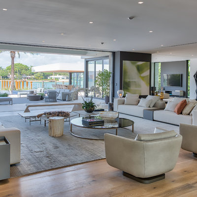 Example of a minimalist formal and open concept light wood floor and brown floor living room design in Miami with white walls