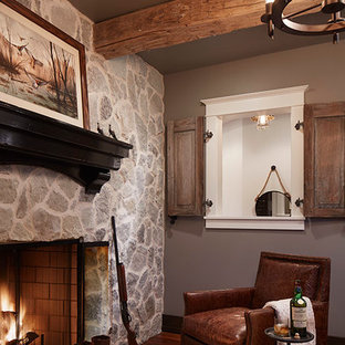 Inspiration for a transitional medium tone wood floor living room remodel in Minneapolis with brown walls, a standard fireplace and a stone fireplace