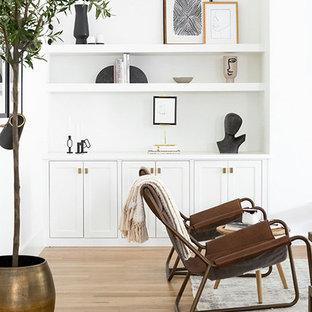 Идея дизайна: большая открытая гостиная комната в стиле модернизм с белыми стенами, светлым паркетным полом, подвесным камином, фасадом камина из штукатурки, телевизором на стене и коричневым полом