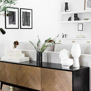 Idéer för att renovera ett stort funkis allrum med öppen planlösning, med vita väggar, ljust trägolv, en hängande öppen spis, en spiselkrans i gips, en väggmonterad TV och brunt golv