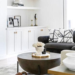 Diseño de salón abierto, minimalista, grande, con paredes blancas, suelo de madera clara, chimeneas suspendidas, marco de chimenea de yeso, televisor colgado en la pared y suelo marrón