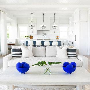 Foto di un grande soggiorno stile marino aperto con sala formale, pareti bianche, parquet chiaro, camino classico, cornice del camino in intonaco, nessuna TV e pavimento beige