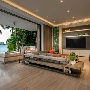 Imagen de salón abierto, contemporáneo, extra grande, sin chimenea, con paredes grises, televisor colgado en la pared, suelo de baldosas de porcelana y suelo beige