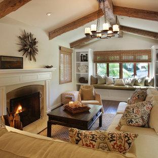 オレンジカウンティの広い地中海スタイルのおしゃれな独立型リビング (標準型暖炉、白い壁、濃色無垢フローリング、タイルの暖炉まわり、テレビなし、茶色い床) の写真
