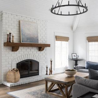 シカゴの広いカントリー風おしゃれなリビング (無垢フローリング、茶色い床、白い壁、標準型暖炉、レンガの暖炉まわり、塗装板張りの天井、三角天井) の写真