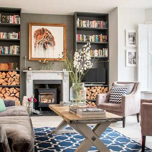 Foto de salón clásico renovado con paredes grises, estufa de leña, pared multimedia y suelo beige