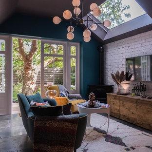 Ispirazione per un soggiorno eclettico di medie dimensioni e chiuso con pareti blu, pavimento in ardesia, TV a parete e pavimento grigio