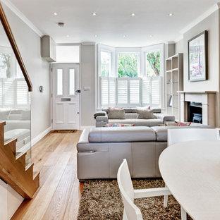 Modelo de salón abierto, moderno, de tamaño medio, con paredes grises, suelo de madera clara, estufa de leña, marco de chimenea de madera y televisor colgado en la pared