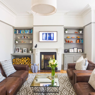 Design ideas for a mid-sized victorian enclosed living room in London with grey walls, light hardwood floors, a wood stove, a tile fireplace surround, a wall-mounted tv and brown floor.