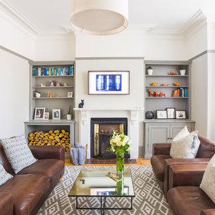 Diseño de salón cerrado, clásico, de tamaño medio, con paredes grises, suelo de madera clara, estufa de leña, marco de chimenea de baldosas y/o azulejos, televisor colgado en la pared y suelo marrón