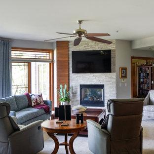 他の地域の中くらいのモダンスタイルのおしゃれなLDK (グレーの壁、無垢フローリング、標準型暖炉、積石の暖炉まわり、壁掛け型テレビ、茶色い床) の写真
