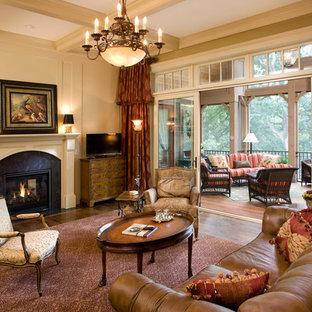 Example of a large classic open concept medium tone wood floor living room design in Minneapolis with beige walls, a tv stand and a two-sided fireplace