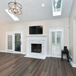 ローリーの中サイズのトランジショナルスタイルのおしゃれな独立型リビング (フォーマル、ベージュの壁、濃色無垢フローリング、標準型暖炉、石材の暖炉まわり、壁掛け型テレビ、白い床) の写真
