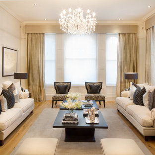 Design ideas for a classic formal living room in London with beige walls and light hardwood flooring.