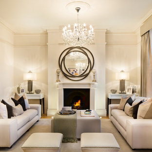 Transitional formal and enclosed light wood floor living room photo in London with beige walls and a standard fireplace