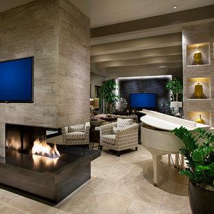 Réalisation d'un grand salon design ouvert avec un sol en marbre, une cheminée double-face, un manteau de cheminée en carrelage, une salle de réception, un mur beige et un téléviseur fixé au mur.
